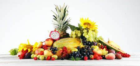 Tropical fruits background, many colorful ripe fruits with strawberries, grapes and cherries on grey table