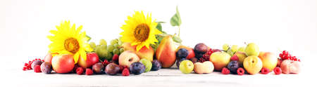 Autumn nature concept. Fall fruit with sunflower and grapes on wood. Thanksgiving dinner. Composition with plums and apples