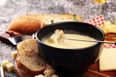Gourmet Swiss fondue dinner on a winter evening with assorted cheeses on a board alongside a heated pot of cheese fondue with two forks dipping bread and white wine behind in a tavern or restaurant Banque d'images