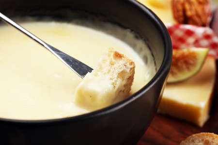 Gourmet Swiss fondue dinner on a winter evening with assorted cheeses on a board alongside a heated pot of cheese fondue with two forks dipping bread and white wine behind in a tavern or restaurant Stock fotó