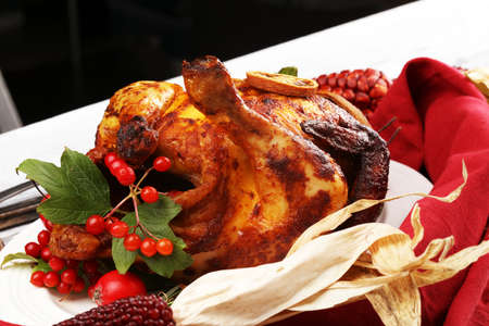 Baked turkey or chicken. The Christmas table is served with a turkey, decorated with fruits, salad and nuts. Fried chicken, table. Christmas dinner.