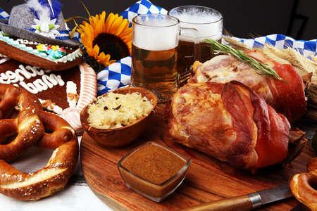 Traditionelle deutsche Küche. Schweinshaxe gebratene Schinkenhaxe. Bier, Brezeln und verschiedene bayerische Spezialitäten. Oktoberfest-Hintergrund Standard-Bild