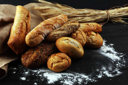 Surtido de pan horneado y panecillos sobre fondo de mesa de madera. Concepto de cartel de panadería Foto de archivo