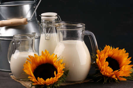 A jug of milk and glass of milk on a wooden table and sunflower Фото со стока - 129789045