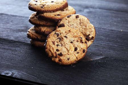 Biscuits au chocolat sur table en bois. Cookies aux pépites de chocolat tourné sur noir Banque d'images