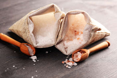 Sea salt and himalayan in burlap. Crystals of salt on rustic table