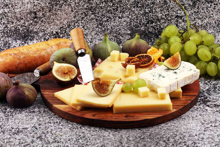 Cheese platter with different cheese and grapes and figs Stok Fotoğraf - 129789214