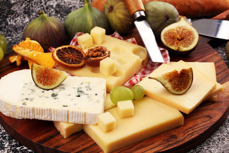 Cheese platter with different cheese and grapes and figs Stok Fotoğraf - 129789239