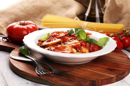 Ravioli with tomato sauce garnished with parmesan cheese and basil on table 免版税图像