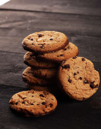 Chocolate cookies on wooden table. Chocolate chip cookies shot on black