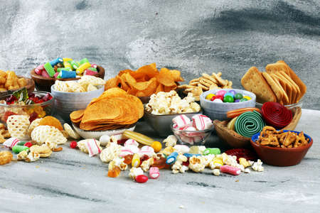 Salty snacks. Pretzels, chips, crackers and candy sweets. Unhealthy products. food bad for figure, skin, heart and teeth. Assortment of fast carbohydrates food.