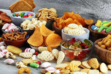 Aperitivos salados. Pretzels, patatas fritas, galletas saladas y caramelos. Productos nocivos para la salud. comida mala para la figura, la piel, el corazón y los dientes. Surtido de comida rápida con carbohidratos. Foto de archivo