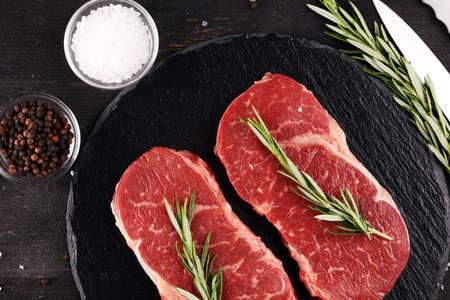 Steak raw. Barbecue Rib Eye Steak or rump steak on rustic table with rosemary