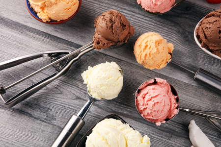Set of ice cream scoops of different colors and flavours with berries, chocolate and fruits on table