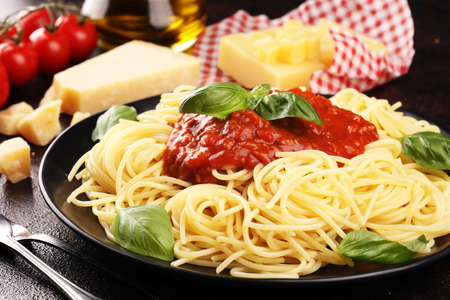 Plate of delicious spaghetti Bolognaise or Bolognese with savory minced beef and tomato sauce garnished with parmesan cheese