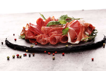 Marble cutting board with prosciutto, bacon, salami and sausages on wooden background. Meat platter appetizers Banco de Imagens