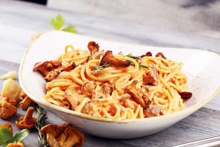 pasta with organic chanterelles. portion of spaghetti pasta with fried chanterelles in a creamy garlic sauce with cheese close-up on a plate on the table.