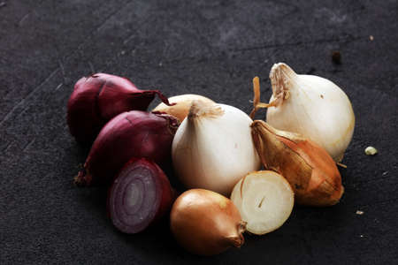 a bunch of different onions on rustic background Banco de Imagens