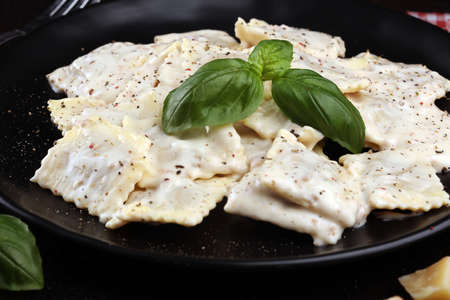 Ravioli with carbonara  garnished with parmesan cheese and basil on table