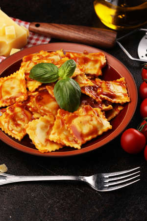 Ravioli with tomato sauce garnished with parmesan cheese and basil on table Banco de Imagens