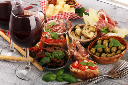 Italian antipasti wine snacks set. Cheese variety, Mediterranean olives, pickles, Prosciutto di Parma, tomatoes, artichokes on table 版權商用圖片