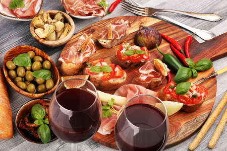 Italian antipasti wine snacks set. Cheese variety, Mediterranean olives, pickles, Prosciutto di Parma, tomatoes, artichokes on table 版權商用圖片 - 131453876