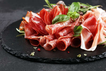 Marble cutting board with prosciutto, bacon, salami and sausages on wooden background. Meat platter appetizers