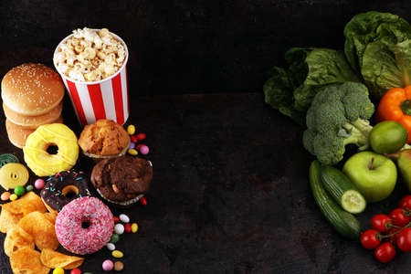 healthy or unhealthy food. Concept photo of healthy and unhealthy food. Fruits and vegetables vs donuts,sweets and burgers on dark