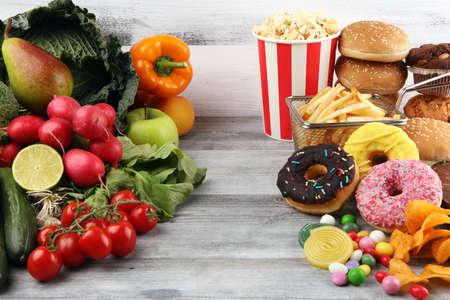 gesundes oder ungesundes Essen. Konzeptfoto von gesundem und ungesundem Essen. Obst und Gemüse vs. Donuts, Süßigkeiten und Burger bei Dunkelheit