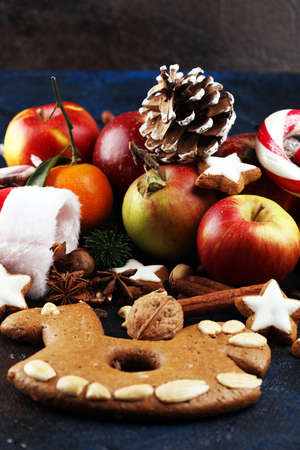 christmas cookies and santa had with spieses, nuts and fruits on table