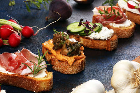 Assorted bruschetta with various toppings. Appetizing bruschetta or brie crostini. Variety of small sandwiches. Mix bruschetta Stock Photo