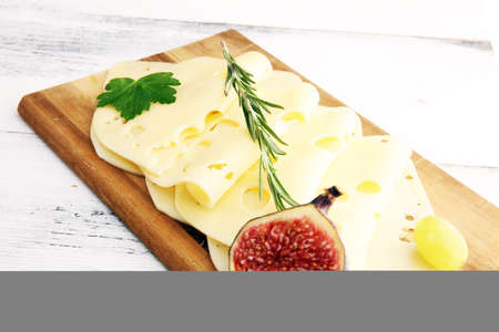 cheese slices on wooden tray with parsley. cheese with whole 版權商用圖片