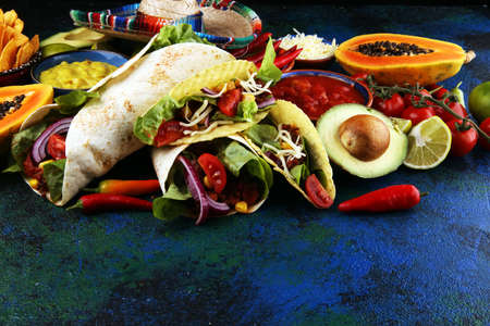 Mexican food, including tacos, guacamole, nachos and pepper on table Imagens