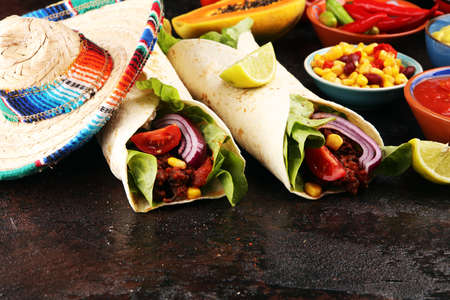 Mexican food, including tacos, guacamole, nachos and pepper on table Stock Photo
