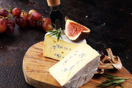 Camembert cheese and rosemary on rustic table Stock Photo