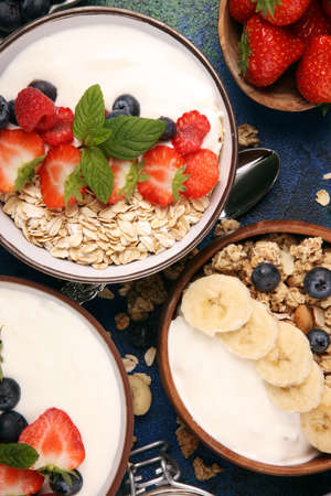 Tasty homemade granola served on table. Healthy breakfast with a bowl of oatmeal with banana, blueberries, raspberries and healthy food for Breakfast
