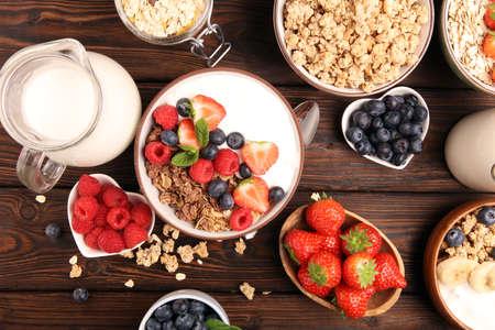 Granola casera sabrosa servida en la mesa. Desayuno saludable con un plato de avena con plátano, arándanos, frambuesas y comida saludable para el desayuno Foto de archivo