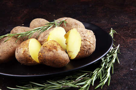 Pile of potatoes lying on a dish. Fresh boiled organic potato and rosemary