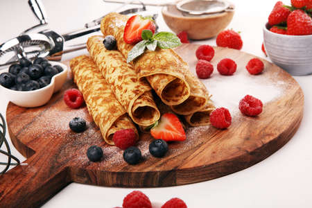 Delicious Tasty Homemade crepes or pancakes with raspberries and mint on table