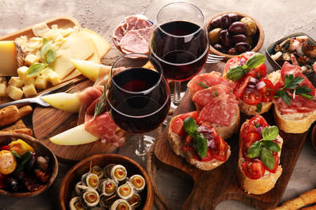 Italian antipasti wine snacks set. Cheese variety, Mediterranean olives, pickles, Prosciutto di Parma, tomatoes, anchovy and wine in glasses over black grunge background Reklamní fotografie