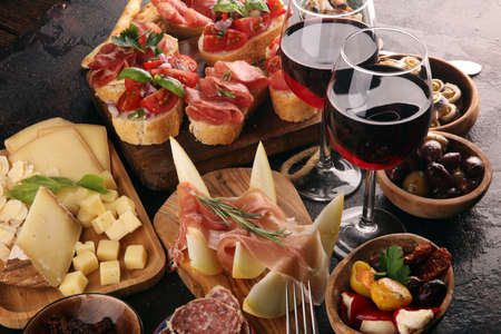 Italiaanse antipasti wijn snacks set. Kaasvariëteit, mediterrane olijven, augurken, Prosciutto di Parma, tomaten, ansjovis en wijn in glazen over zwarte grungeachtergrond Stockfoto