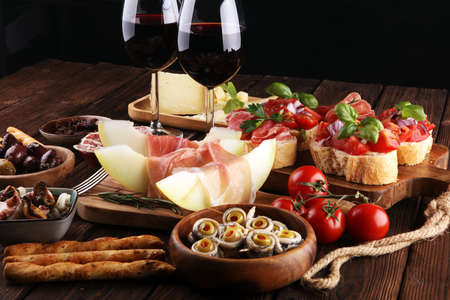 Italian antipasti wine snacks set. Cheese variety, Mediterranean olives, pickles, Prosciutto di Parma, tomatoes, anchovy and wine in glasses over black grunge background Banque d'images