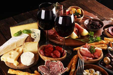 Ensemble de collations au vin antipasti italien. Variété de fromage, olives méditerranéennes, cornichons, prosciutto di Parma, tomates, anchois et vin dans des verres sur fond grunge noir