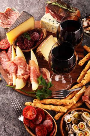 Ensemble de collations au vin antipasti italien. Variété de fromage, olives méditerranéennes, cornichons, prosciutto di Parma, tomates, anchois et vin dans des verres sur fond grunge noir Banque d'images