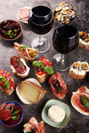 Appetizers table with italian antipasti snacks and wine in glasses. Brushetta or authentic traditional spanish tapas set, cheese variety board