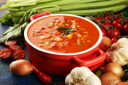 Minestrone soup  with tomato in a pan on a light table, top view. Italian soup with pasta and seasonal vegetables. Delicious vegetarian food concept.