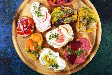 Assorted bruschetta with various toppings. Appetizing bruschetta or brie crostini. Variety of small sandwiches. Mix bruschetta