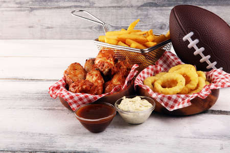 chicken wings, fries and onion rings for football on a table. Great for Bowl football Game