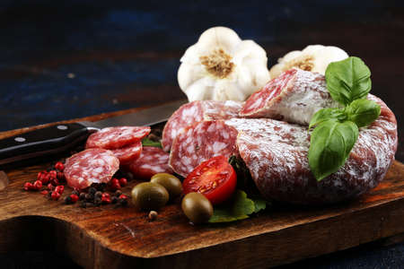 thinly sliced salami on a wooden texture on the background