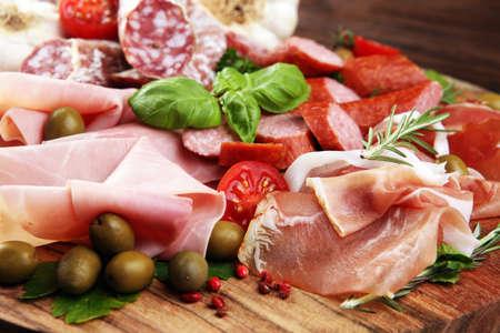 Vassoio con delizioso salame, fette di prosciutto crudo, salsiccia e basilico. Piatto di carne con selezione. Archivio Fotografico